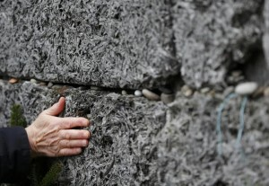 A survivor touches the 'Wall of Death' in the former Nazi German concentration and extermination camp Auschwitz in Oswiecim