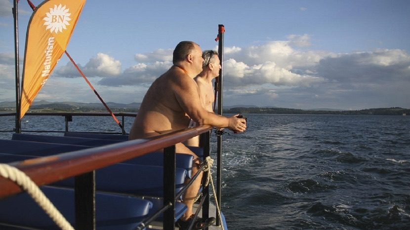 Members of British Naturism enjoy a sunny evening cruise to celebrate the organisations 50th anniversary on the Firth of Forth Scotland UK 5 July 2014.